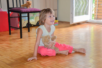 beautiful little girl sitting on the floor and laughing