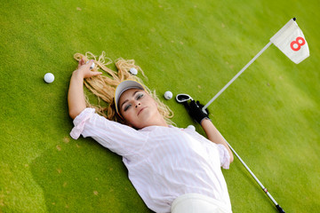 Portrait of beautiful woman relaxing during playing golf on a green field outdoors background