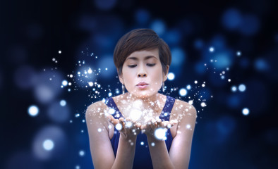 Beauty woman blowing magic dust and glowing bubbles from her hands. Magical Concept. Isolated on dark blue background