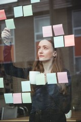 Business executive looking at sticky note while having cup of coffee in office
