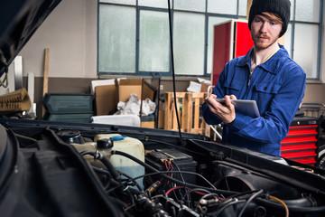 Mechanic Checking A Car Engine Using Digital Tablet