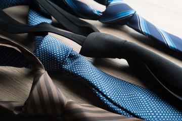 Silk neck ties on wooden background.