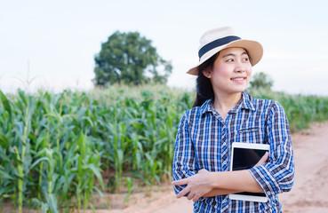 Asian woman farmer holding tablet in corn field