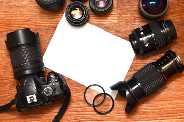 Still life with a set of professional photographer. Camera with a lot of lenses and photo accessories on brown wooden surface with a site for the text in the form of a sheet of paper