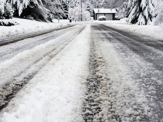 Snow covered road in residential district