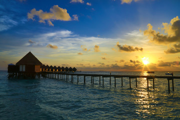 Beautiful sunset with water villas in tropical Maldives island..