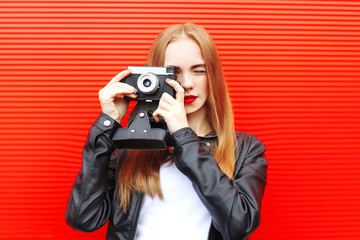 Fashion pretty woman with vintage camera in city over red backgr