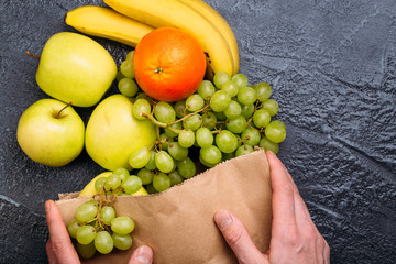 Food background of fresh fruit bananas oranges apples and grapes in shopping bag on black table Healthy lifestyle Top view Copy space