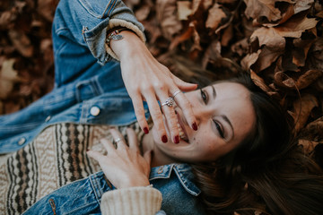 Happy female in fallen leaves