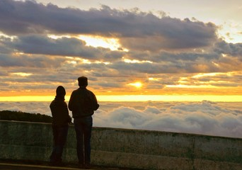 Silhouette couple looking at the beautiful sunrise on the top of