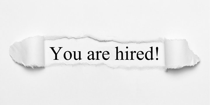 You are hired! on white torn paper