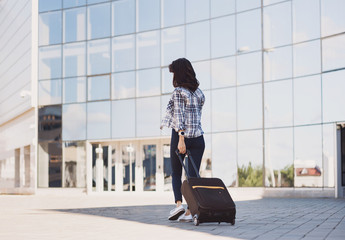 Young woman walking with luggage suitcase. Vacations, travel and active lifestyle concept