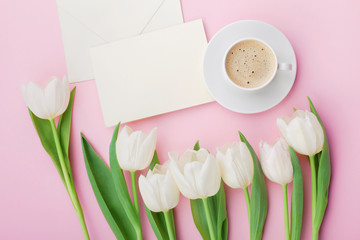 Coffee mug, paper card and spring tulip flowers for good morning on pink table from above in flat lay style. Breakfast on Mothers or Womens day.