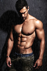 Portrait of strong healthy handsome Athletic Man Fitness Model posing near dark gray wall in the rain