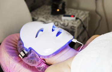 Photodynamic therapy facial mask on woman's face