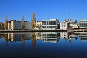 Colorful trees and buildings mirroring in the river Rhine
