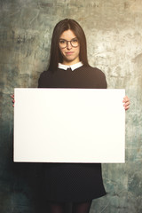 Lovely girl in glasses and dress posing with white canvas. Horizontal mockup