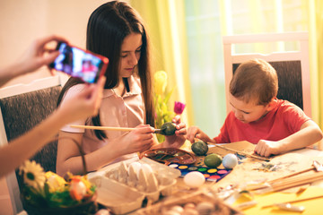 Mother with phone photographing children while they paint Easter