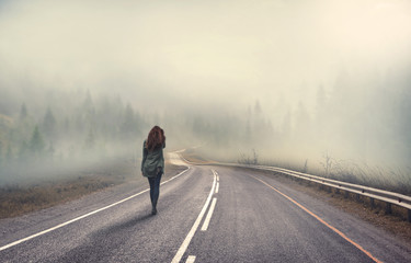 girl walking alone on mountain highway in winter foggy day Wall mural