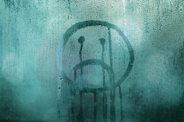 Unhappy hand drawn emoji on wet rainy glass window. Cyan blue color filter effect and selective focus used.