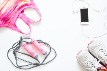 Flat lay of cellphone, pink sport bra, jump rope and sneaker on