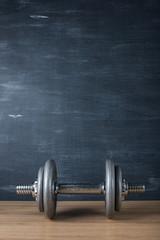 metal barbell on dark gray background