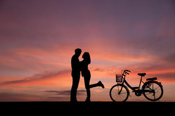 Silhouette of lovers standing hug and kiss with vintage bikes on the side.The background image is a sunset in Thailand.