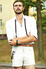 944b4d755349 Handsome hipster model man in stylish summer clothes posing on ...
