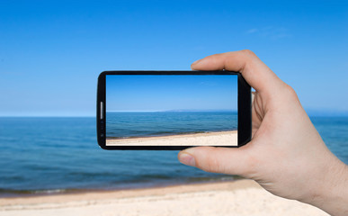 A man  hand holding smart phone making photo on smartphone mobile closeup sea view