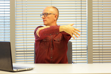 middle age balding man relaxing neck - stretching arm - short break for exercise on chair in office