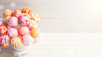 Bright cake pops in ray of light   on white wooden background.