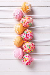Bright cake pops on white  painted wooden background.