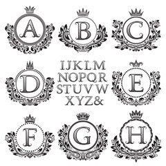 Vintage monogram kit. Black patterned letters and floral coat of arms frames for creating initial logo in antique style.