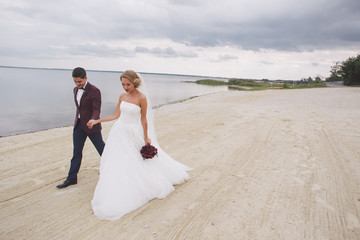Beautiful couple in wedding day on the coast of the lake.