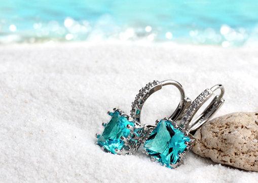 Jewelry earrings with aquamarine on sand beach background, soft