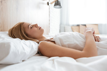 Side view of young woman sleeping on bed