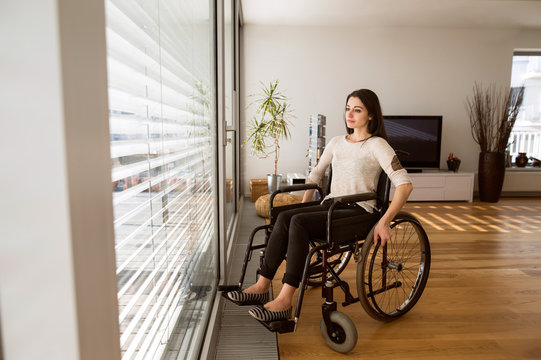 Upset disabled woman in wheelchair at home in living room.