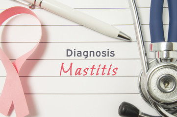 Diagnosis Mastitis. Pink ribbon as symbol of struggle with breast diseases and stethoscope lying on medical form with text labels Diagnosis Mastitis. Concept for branch of medicine of breast diseases