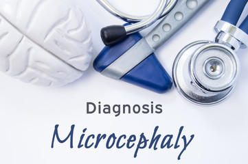 Diagnosis of Microcephaly. Anatomical brain figure, neurological hammer and stethoscope lying on sheet of paper or book with the title neurological diagnosis of Microcephaly. Concept for neurology