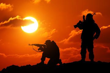 Two men shot dead a soldier holding a gun and Vit mountain piktureskie bakkdrop al sunset