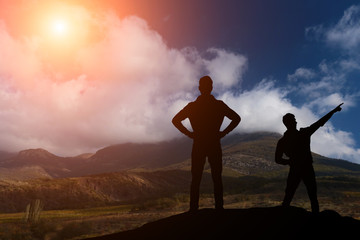 silhouette of two men standing on a rock looking into the distance