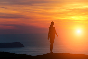 silhouette of a girl standing on a hill looking directly at the background of a beautiful sunset and the sea