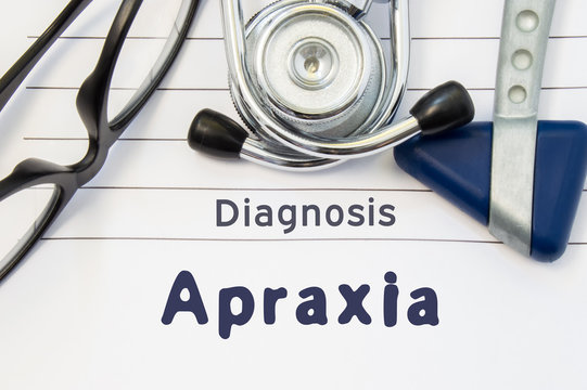 Neurological diagnosis of Apraxia. Neurological hammer, stethoscope and doctor's glasses lie on doctor workplace on sheet of notebook, labeled with the title of medical diagnosis of Apraxia