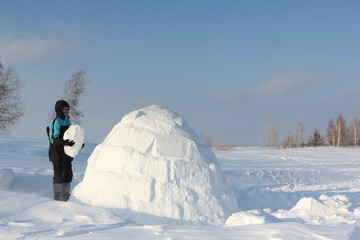 Man building an igloo  in a blizzard in the winter