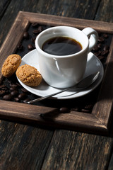 cup of black coffee and cookies on a wooden tray