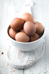 Chicken eggs  in the ceramic bowl on the white wooden table  vertical