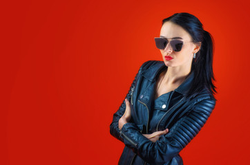 Strict beautiful woman with black hair in a leather jacket