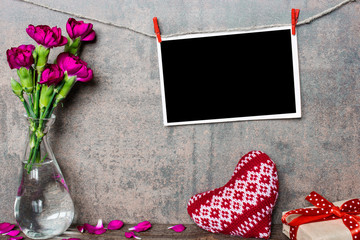 mock up blank photo frame hanging on rope with purple carnation