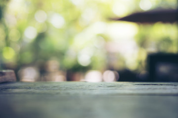 Blur and bokeh image of wooden table with green nature