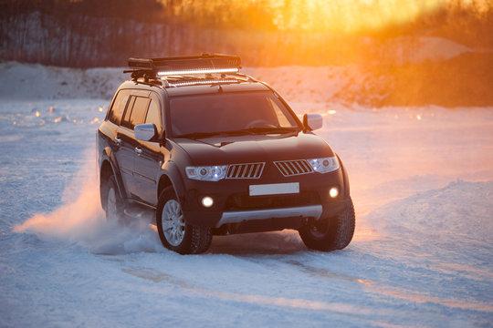 Black SUV moving on ice at sunset